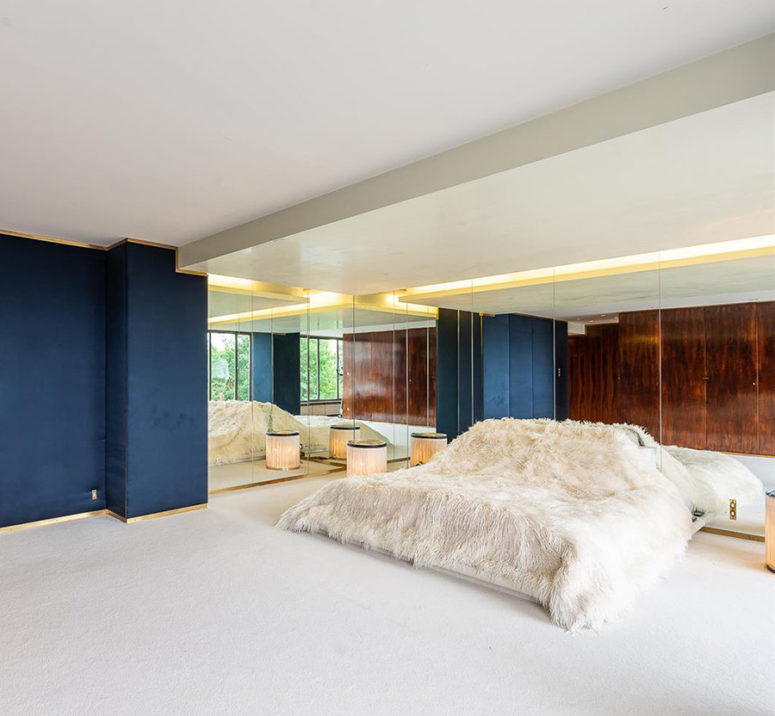 07-The-master-bedroom-is-done-with-a-large-bed-mirror-walls-and-much-negative-space-for-an-airy-feeling-775x716