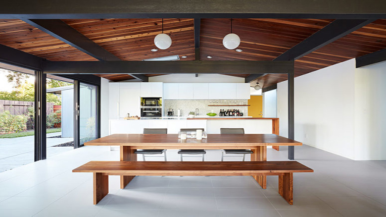 02-The-main-space-is-an-open-layout-with-a-kitchen-dining-and-living-space-with-a-glazed-wall-and-skylights-775x517
