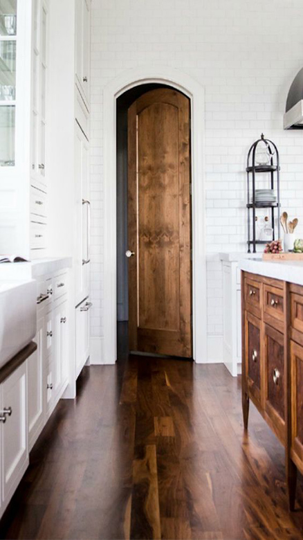 02-white-kitchen-with-a-stained-hardwood-floor-and-wood-island-and-door