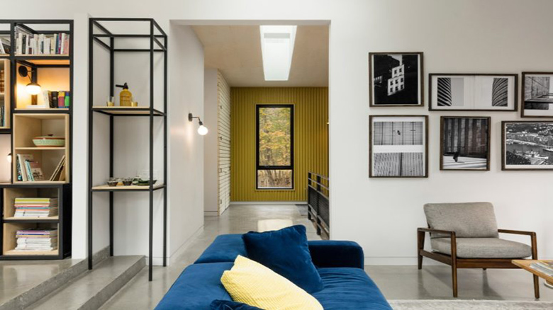 05-Bodl-touches-like-this-blue-sofa-and-yellow-pillows-add-interest-to-the-space-775x517