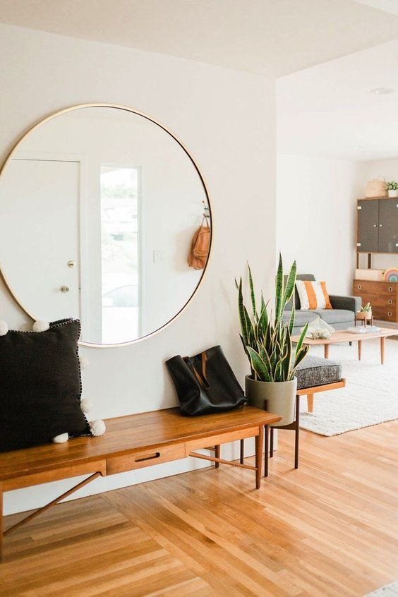 05-an-airy-mid-century-modern-entryway-with-an-oversized-round-mirror-and-a-cool-bench