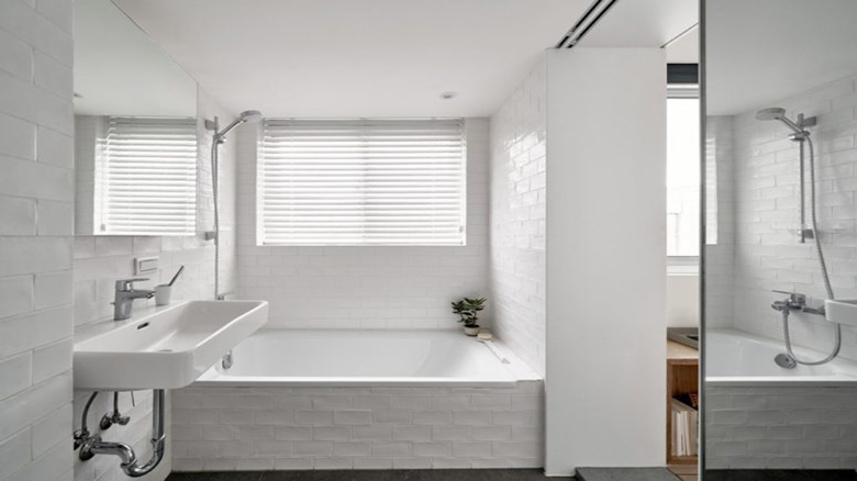 06-The-bathroom-is-clad-with-white-tiles-theres-a-covered-window-to-have-natural-light-yet-privacy-775x498