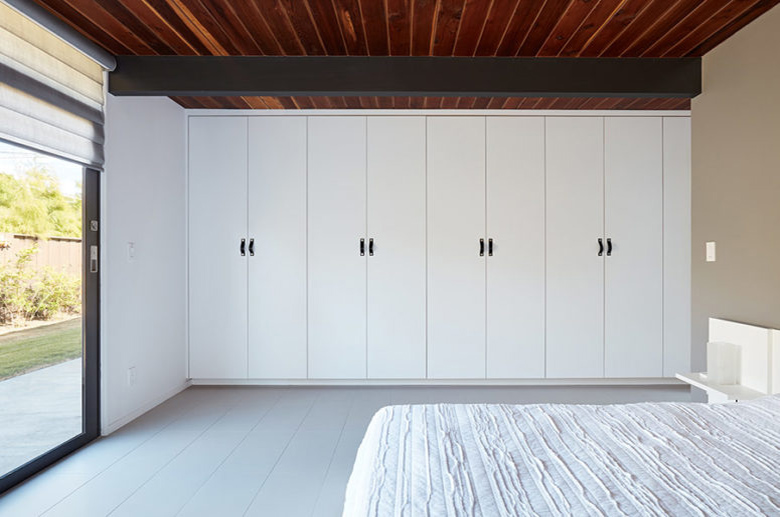 06-The-master-bedroom-is-very-laconic-its-done-in-white-with-a-large-bed-some-cabinets-and-bedside-tables-775x517