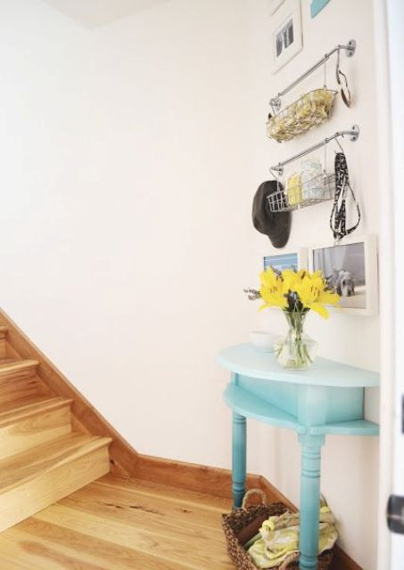 09-a-stairwell-landing-is-an-awkward-nook-its-decorated-with-a-half-table-in-blue-and-some-hanging-shelves