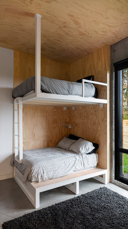 10-The-guest-bedroom-features-a-bunk-bed-a-fluffy-rug-and-much-natural-light